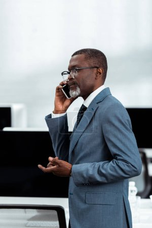 Photo for Handsome african american businessman talking on smartphone in office - Royalty Free Image