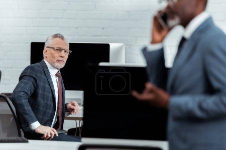 Photo pour Foyer sélectif de bel homme d'affaires en costume regardant partenaire américain africain - image libre de droit