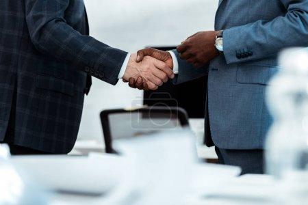 Photo pour Vue recadrée de l'homme d'affaires américain africain se serrant la main avec le associé dans le bureau - image libre de droit