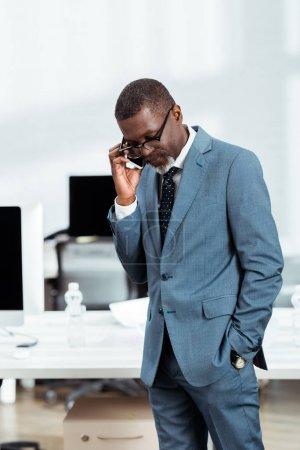 Photo pour Bel homme d'affaires afro-américain en lunettes parlant sur smartphone au bureau - image libre de droit