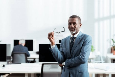 selective focus of african american businessman holding glasses in office