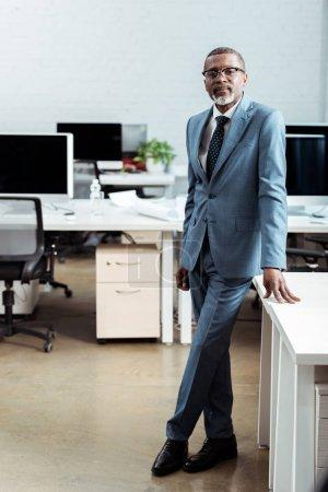 Photo pour Bel homme américain africain dans des glaces restant dans le procès dans le bureau moderne - image libre de droit