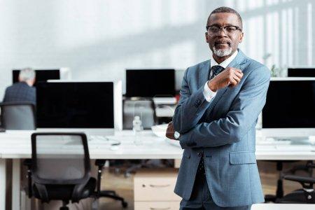 Photo pour Foyer sélectif de l'homme d'affaires afro-américain en lunettes et vêtements formels debout dans le bureau - image libre de droit
