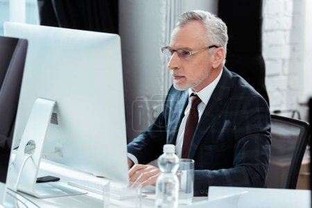 Photo for Selective focus of businessman in glasses working in modern office - Royalty Free Image