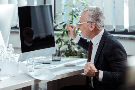 Photo pour Homme d'affaires heureux dans des glaces faisant des gestes près du moniteur d'ordinateur avec l'écran blanc - image libre de droit