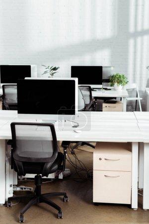 Photo pour Moniteur d'ordinateur avec écran blanc sur le bureau près de la chaise dans le bureau moderne - image libre de droit