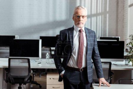 Foto de Handsome businessman in glasses standing with hand in pocket in office - Imagen libre de derechos