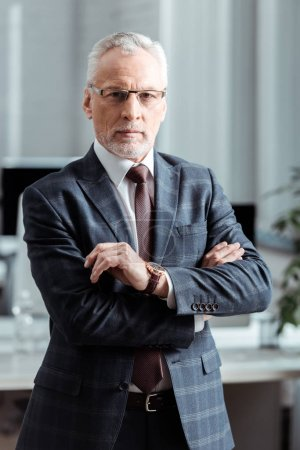 Photo for Handsome businessman in glasses standing with crossed arms in office - Royalty Free Image