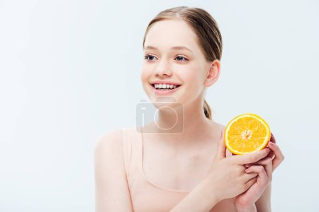 Photo for Happy smiling teenager holding orange half and looking away isolated on grey - Royalty Free Image