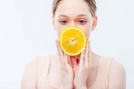 Photo pour Adolescente retenant la moitié orange mûre devant la bouche d'isolement sur le blanc - image libre de droit