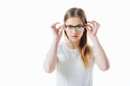 Photo pour Adolescente grave touchant des lunettes et regardant l'appareil-photo isolé sur le blanc - image libre de droit