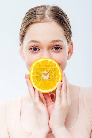 Photo pour Adolescente retenant l'orange mûr devant la bouche d'isolement sur le gris - image libre de droit