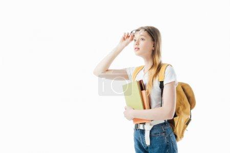 Photo pour Curieuse écolière avec sac à dos tenant des livres et regardant loin isolé sur blanc - image libre de droit