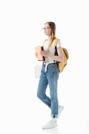 Photo for Smiling schoolgirl with backpack holding books and walking isolated on white - Royalty Free Image