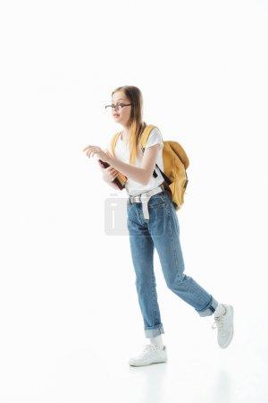Photo pour Écolière dans des glaces avec des livres de fixation de sac à dos et marchant isolé sur le blanc - image libre de droit