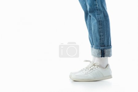 Photo for Cropped view of teenage girl legs in white sneakers and blue jeans isolated on white - Royalty Free Image