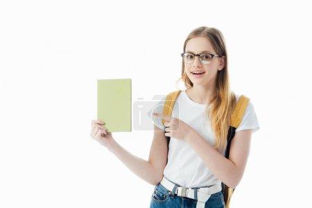 Photo pour Écolière souriante avec sac à dos pointant du doigt au livre isolé sur blanc - image libre de droit