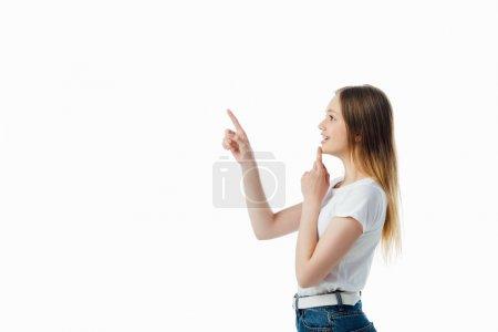Photo pour Vue de côté de la fille d'adolescent gai e pointant avec le doigt d'isolement sur le blanc - image libre de droit