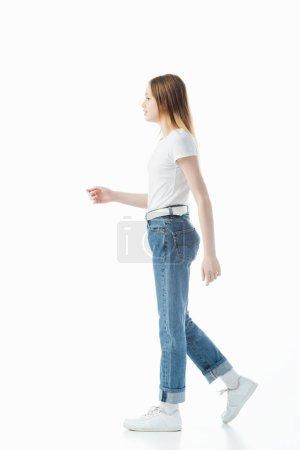 Foto de Vista lateral de la adolescente en jeans azules y camiseta blanca caminando aislado en blanco - Imagen libre de derechos
