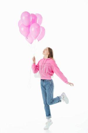 Photo pour Vue pleine longueur de l'adolescente heureuse regardant les ballons roses isolés sur le blanc - image libre de droit