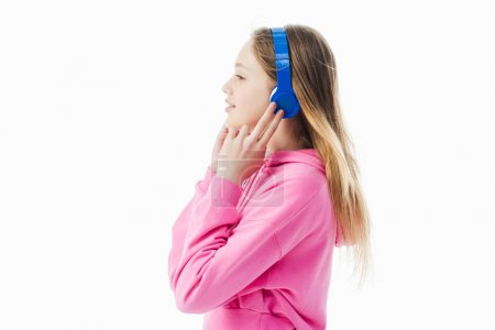 Photo for Side view of smiling teenage girl touching blue headphones on head isolated on white - Royalty Free Image
