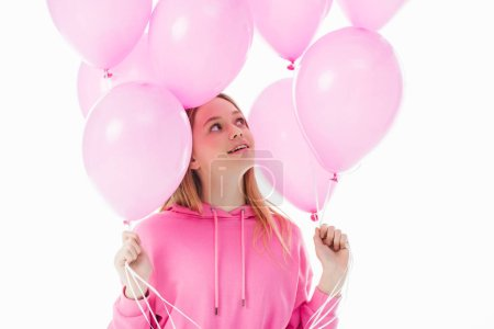 happy teenage girl looking at pink balloons isolated on white