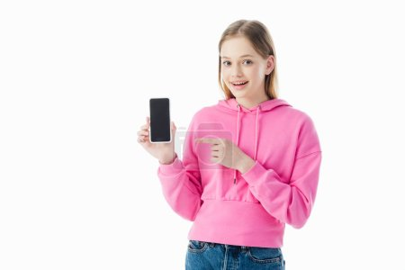 Photo for Happy teenage girl in pink hoodie pointing with finger at smartphone isolated on white - Royalty Free Image