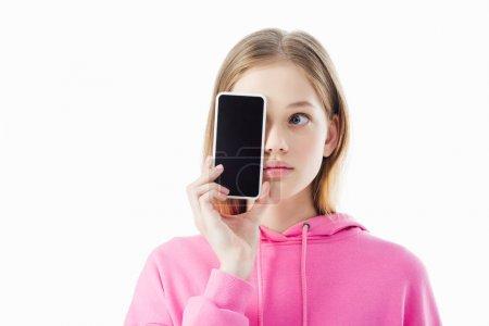 Photo pour Adolescente dans le smartphone rose de fixation de capuche avec l'écran blanc devant le visage d'isolement sur le blanc - image libre de droit