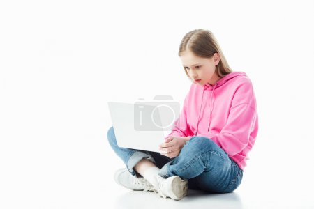 Photo for Upset teenage girl with crossed legs using laptop isolated on white, illustrative editorial - Royalty Free Image