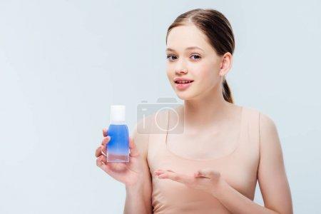 Photo pour Jolie adolescente présentant la lotion cosmétique d'isolement sur le gris - image libre de droit