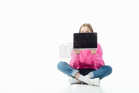 Photo for Teenage girl with obscure face in lotus pose holding laptop with blank screen isolated on white, illustrative editorial - Royalty Free Image