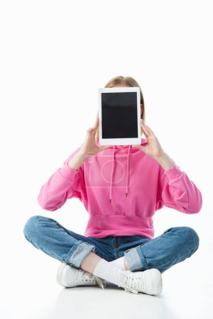 Photo for Teenage girl in lotus pose holding digital tablet with blank screen isolated on white - Royalty Free Image