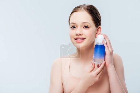 Photo pour Jolie adolescente retenant la lotion bleue d'isolement sur le gris - image libre de droit