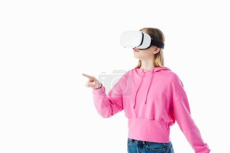 Photo pour Adolescente dans le chandail à capuchon rose utilisant le casque de VR et pointant avec le doigt d'isolement sur le blanc - image libre de droit