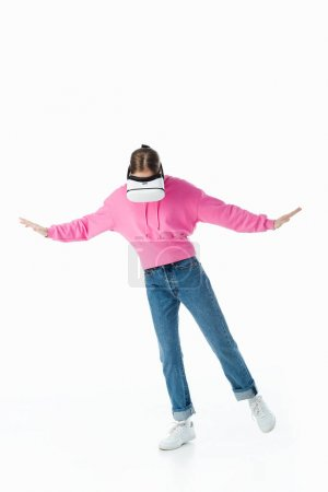 Photo for Teenage girl in pink hoodie and blue jeans wearing vr headset and gesturing isolated on white - Royalty Free Image