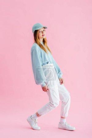 Photo pour Femme adolescente jolie élégante dans le chapeau regardant l'appareil-photo sur le rose - image libre de droit