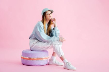 Photo for Pretty teenage girl in cap sitting on decorative macaroon on pink - Royalty Free Image