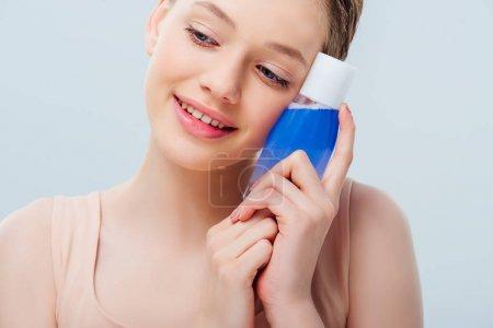 Photo pour Près de vue vers le haut de la jolie adolescente retenant la lotion cosmétique d'isolement sur le gris - image libre de droit