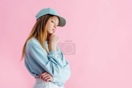 Photo for Thoughtful sad pretty teenage girl in cap isolated on pink - Royalty Free Image