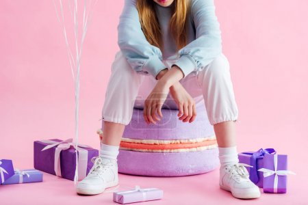 Photo for Cropped view of teenage girl sitting on decorative macaroon near presents on pink - Royalty Free Image
