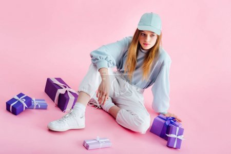 Photo for Pretty teenage girl in cap sitting near presents on pink - Royalty Free Image