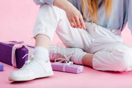 Photo for Cropped view of teenage girl sitting near presents on pink - Royalty Free Image