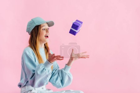 Photo for Excited pretty teenage girl in cap throwing gift in air isolated on pink - Royalty Free Image
