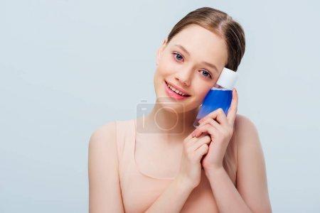 Photo pour Jolie adolescente retenant la lotion cosmétique bleue d'isolement sur le gris - image libre de droit