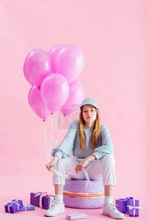 Foto de Adolescente en gorra sentada en macarión decorativo con globos cerca de regalos en rosa - Imagen libre de derechos