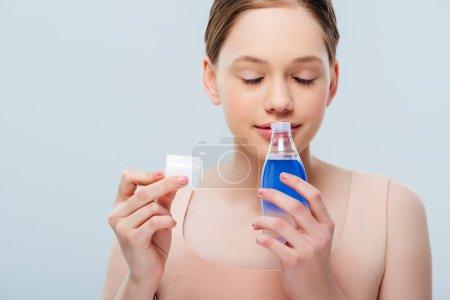 Photo pour Adolescente de sourire avec les yeux fermés sentant la lotion cosmétique d'isolement sur le gris - image libre de droit