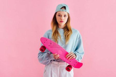 Photo for Pretty teenage girl in cap holding penny board isolated on pink - Royalty Free Image
