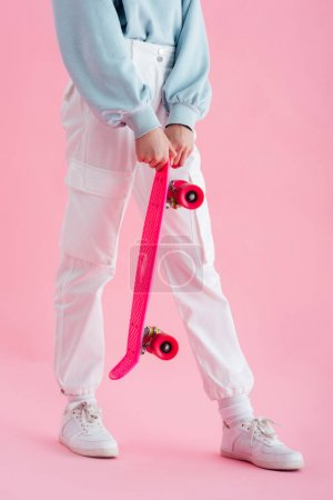 Photo for Cropped view of teenage girl holding penny board on pink - Royalty Free Image