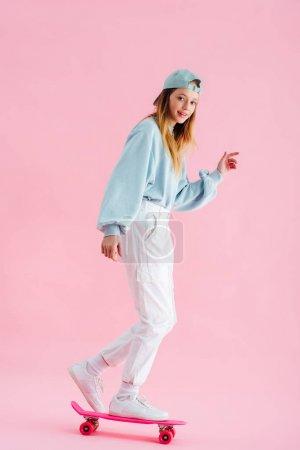 Photo pour Heureuse jolie adolescente dans le chapeau équitation penny board sur rose - image libre de droit