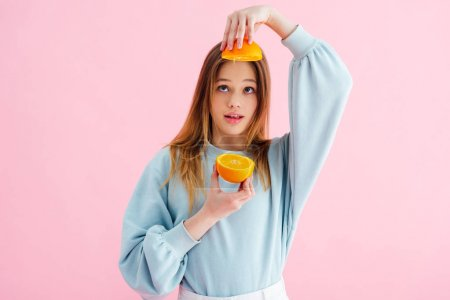 Photo for Pretty teenage girl looking at orange halves isolated on pink - Royalty Free Image